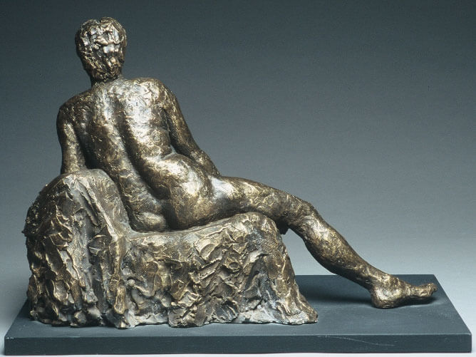Male figure reclining against a cushion back view in cast resin by William Casper.