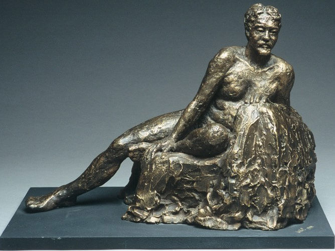 Male figure reclining against a cushion in cast resin by William Casper.