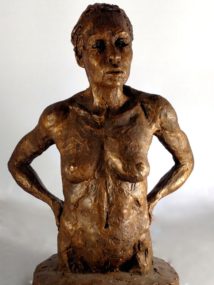 Female with hands on hips looking confidently in resin cast by William Casper.