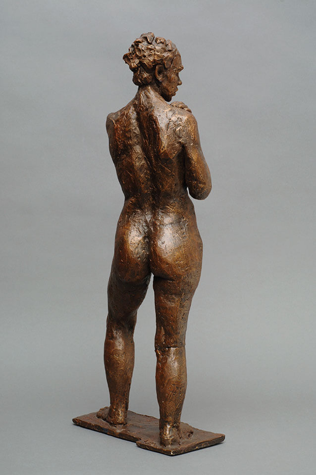 Female standing looking over right shoulder holding left wrist rear view in cast resin by William Casper.
