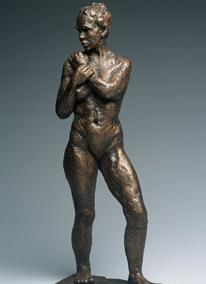 Female standing looking over right shoulder holding left wrist in cast resin by William Casper.