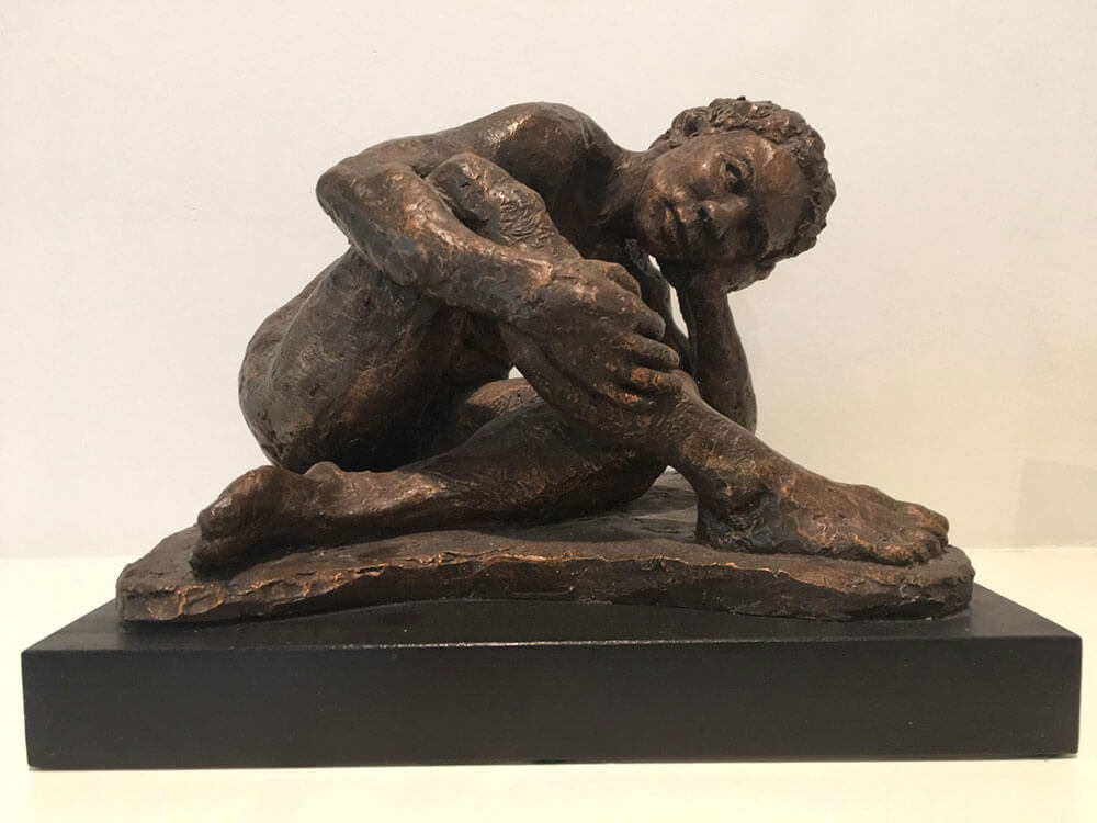 Twisted seated female figure resting on left arm in cast resin by William Casper.