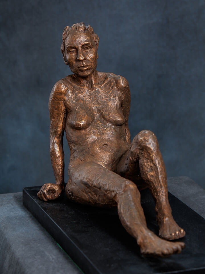 Seated female with leaning back with outstretched legs in cast resin by William Casper