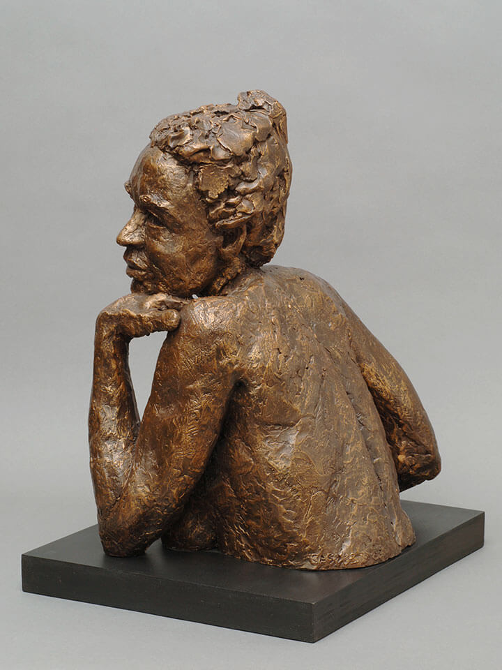 Female chest high torso leaning on left hand gazing out side view in resin cast by William Casper.