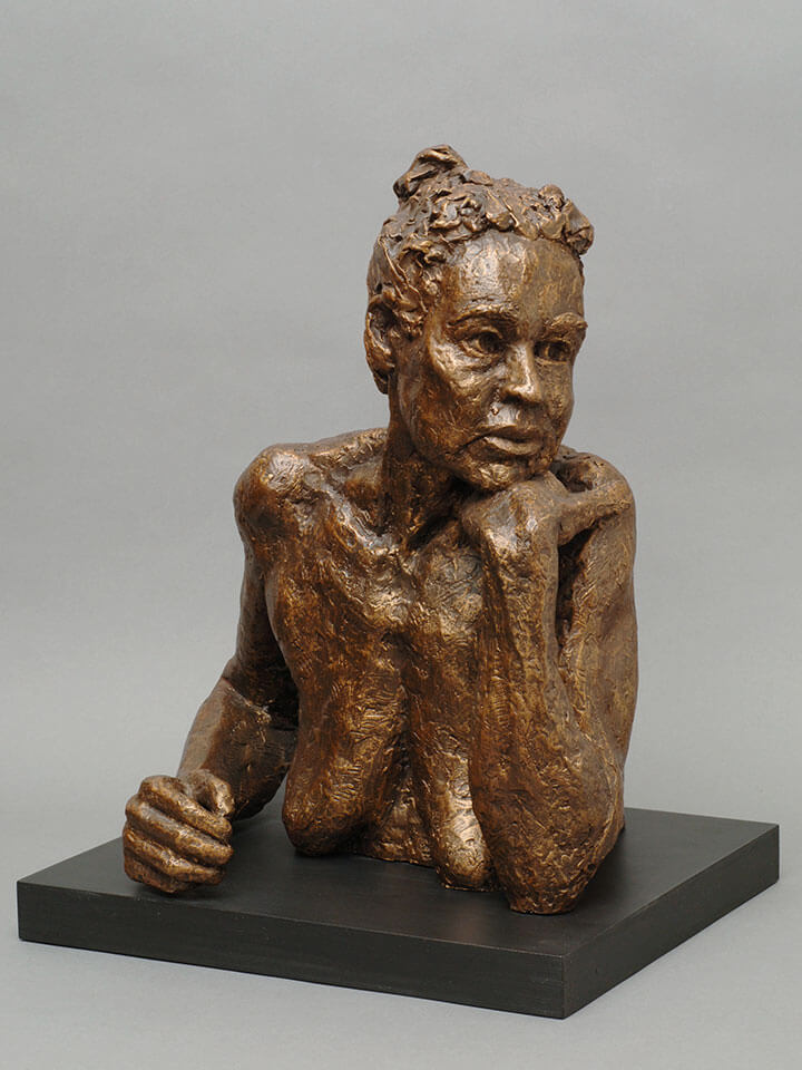 Female chest high torso leaning on left hand gazing out in resin cast by William Casper.