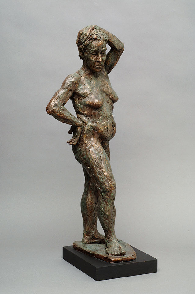 Standing mature woman looking downward side view in cast resin by William Casper