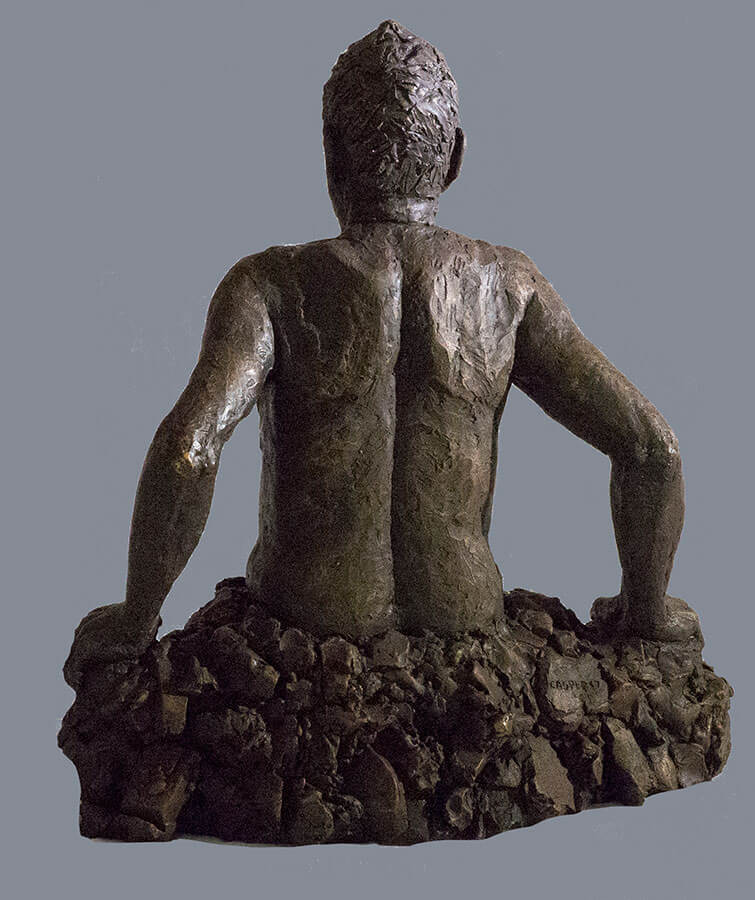 Waist high male figure emerging out of rocks rear view in cast resin by William Casper.