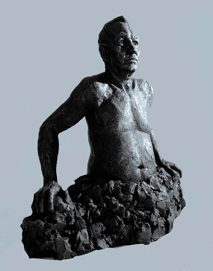Waist high male figure emerging out of rocks side view in cast resin by William Casper.