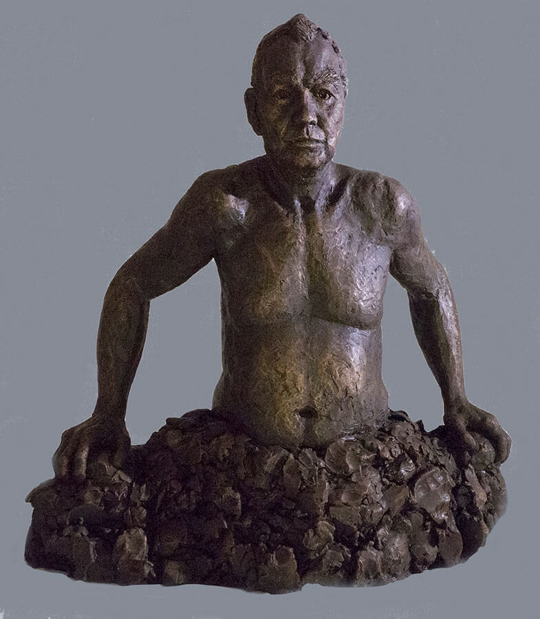 Waist high male figure emerging out of rocks in cast resin by William Casper.