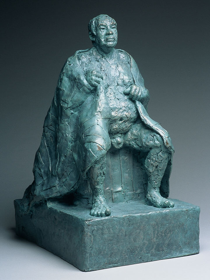 Seated male figure with patchwork cape in fiberglass cast by William Casper.