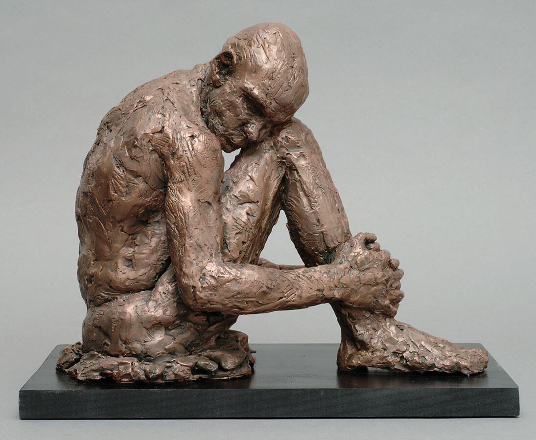 Male seated figure hugging his only leg right side in cast resin by William Casper.