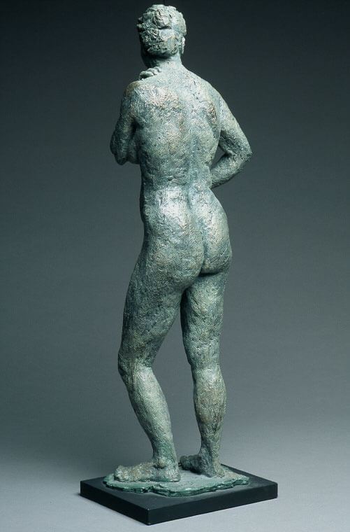 Standing female with left arm crossing left breast rear view in cast resin by William Casper.