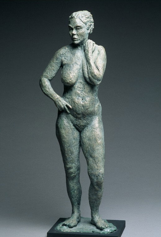 Standing female with left arm crossing left breast in cast resin by William Casper.