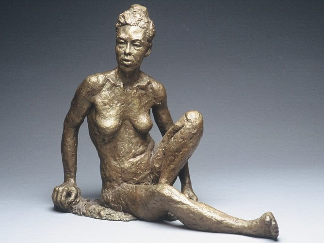 Seated female figure with one leg outstretched in bronze by William Casper
