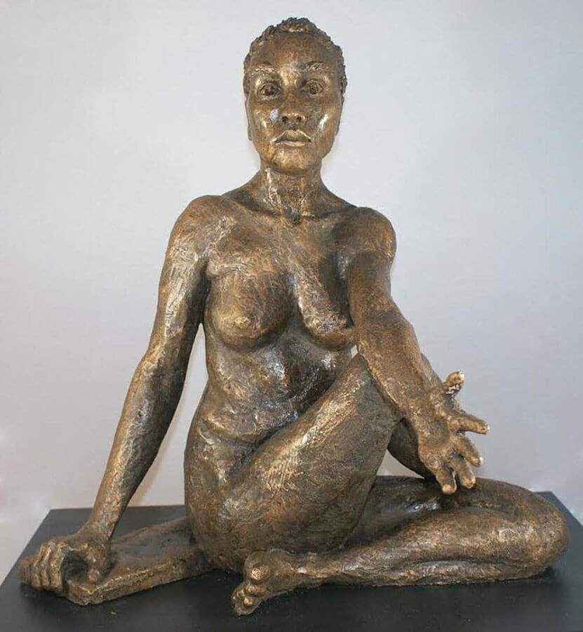 Female in seated and twisted Lord of the Fishes yoga pose in cast resin by William Casper.