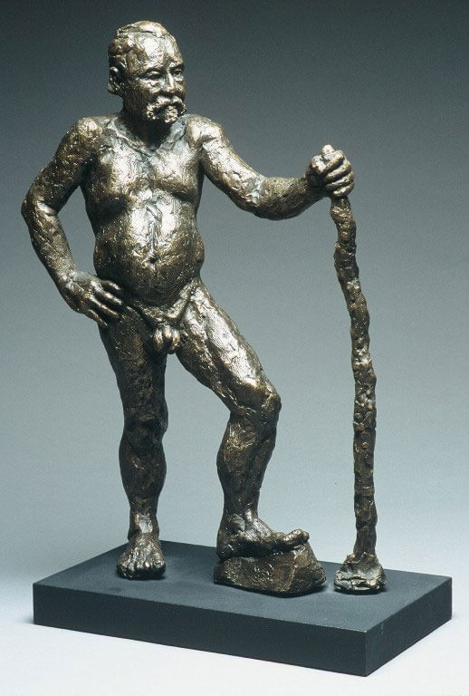 Male figure leaning on walking stick in cast resin by William Casper