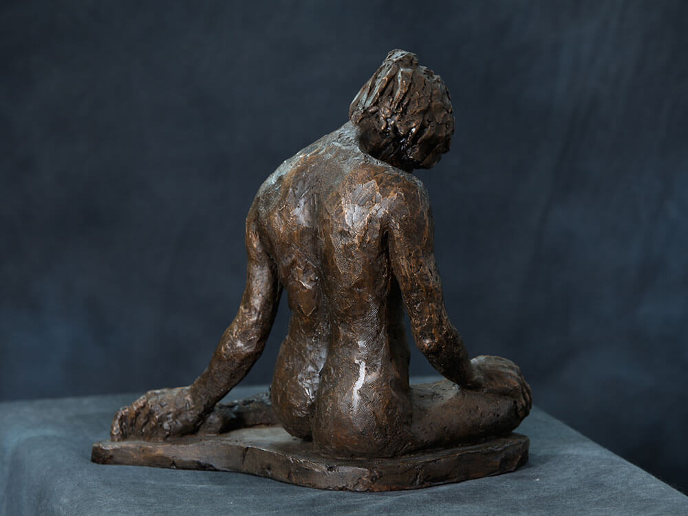 Female sitting with legs folded under reflecting downward rear view in resin cast by William Casper.