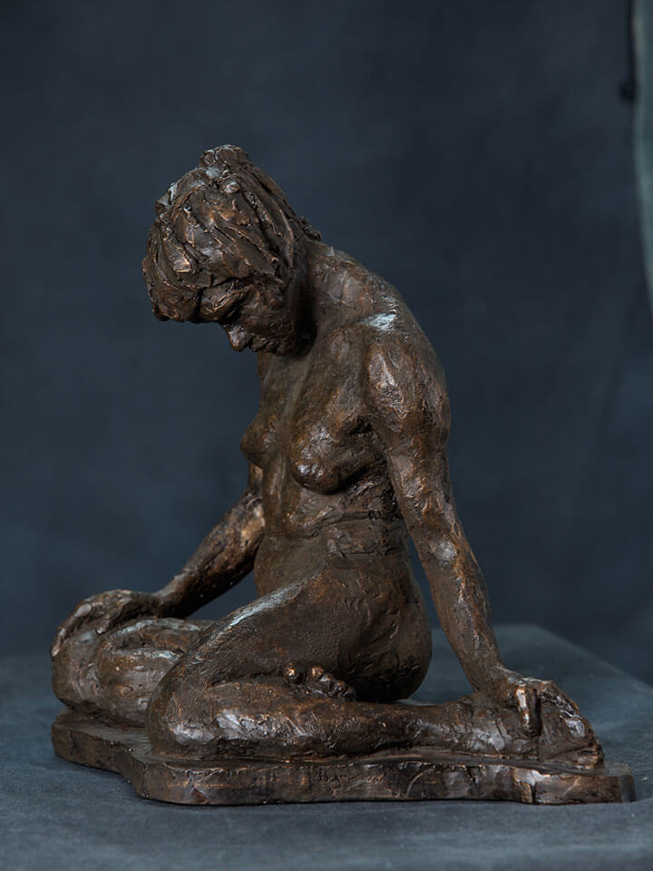 Female sitting with legs folded under reflecting downward side view in resin cast by William Casper.