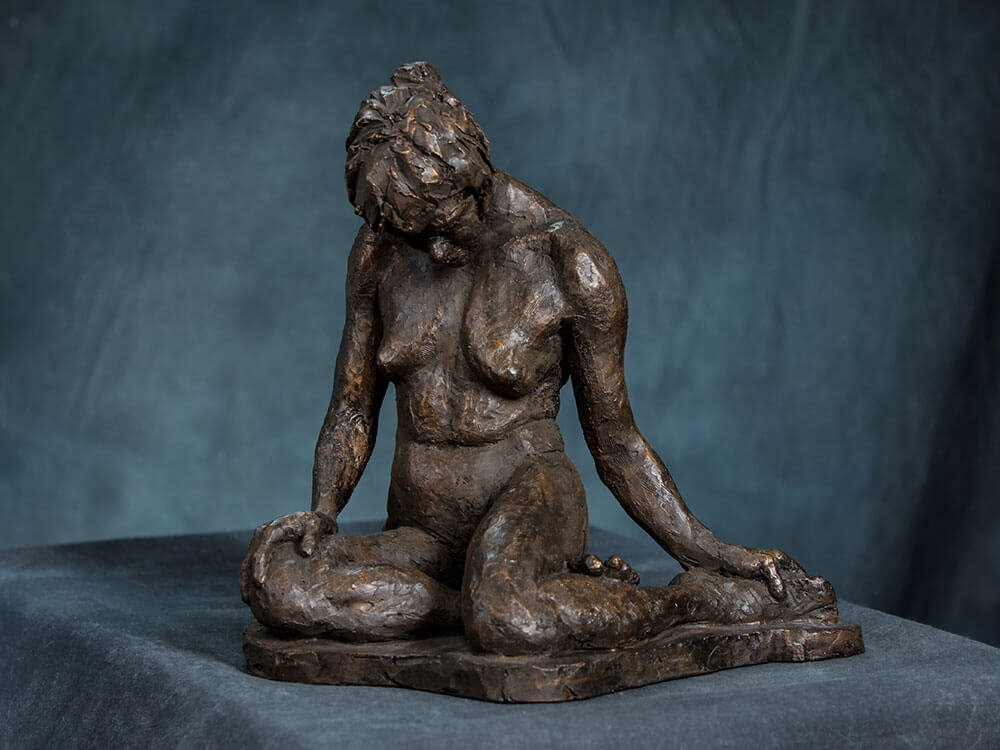 Female sitting with legs folded under reflecting downward in resin cast by William Casper.
