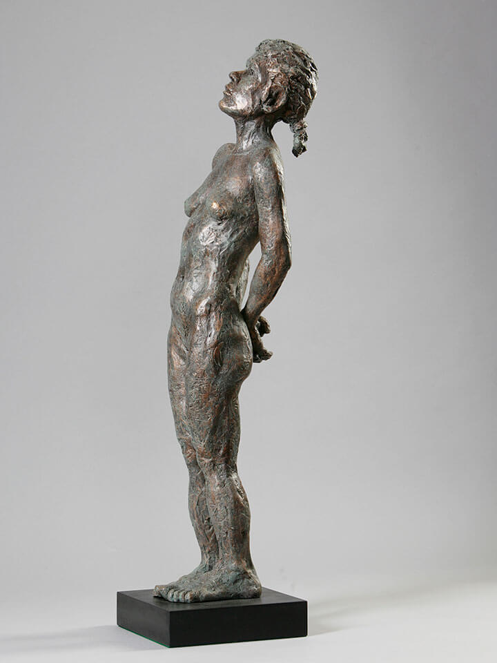 Standing female with back bend, hands behind, and thoughtful contemplation left side in cast resin by William Casper.