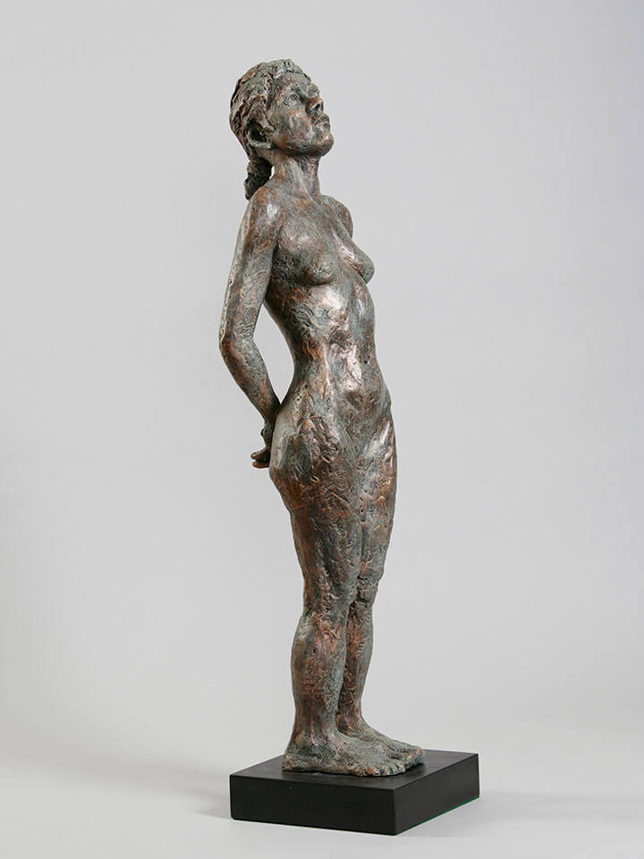 Standing female with back bend, hands behind, and thoughtful contemplation right side in cast resin by William Casper.