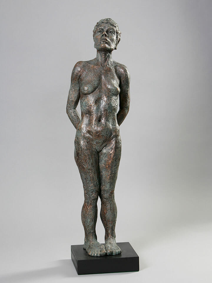 Standing female with back bend, hands behind, and thoughtful contemplation in cast resin by William Casper.