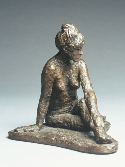 Female seated with one leg outstretched and one leg folded right side in cast plaster by William Casper.