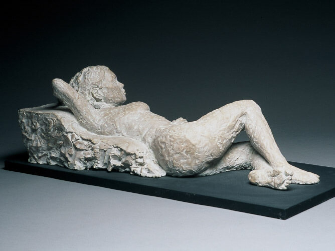 Female reclining against a cushion side view in cast resin by William Casper.