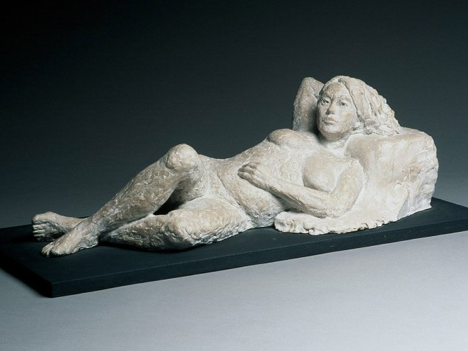 Female reclining against a cushion in cast resin by William Casper.