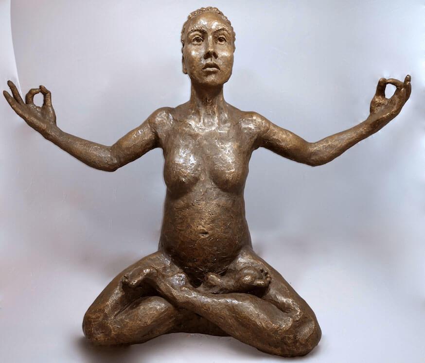Female sitting cross legged in Surrender yoga pose in cast resin by William Casper.