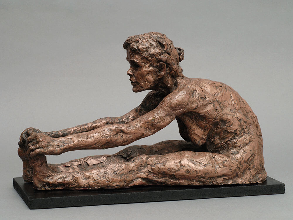 Mature female seated figure with hands over out stretched legs side view in concrete by William Casper.