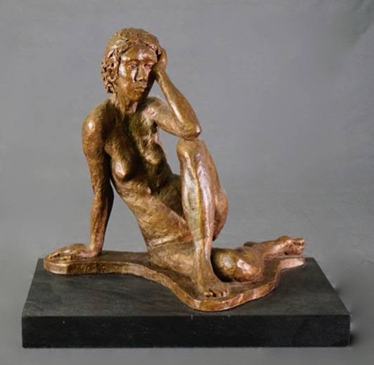 Seated female leaning left arm on left leg in cast resin by William Casper.