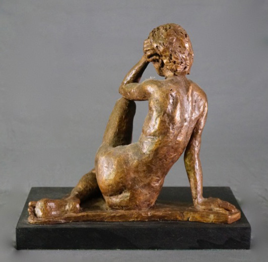 Seated female leaning left arm on left leg rear view in cast resin by William Casper.